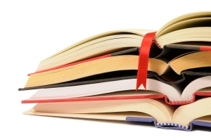 Small pile of open books with red bookmark ribbon isolated on wh
